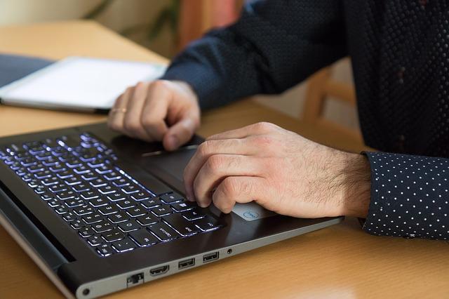 PCのキーボードと男性の手